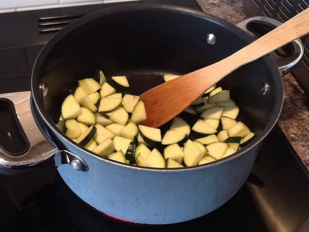 Cooking the courgette quarter slices in olive oil